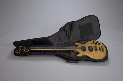 "2015.212a: An electric bass guitar used by Robert ""Kool"" Bell of Kool and the Gang. The bass guitar is made of light coloured wood and has brass tuning pegs. It has two pickups in black. The strings are attached to an oval shaped metal tailpiece with four smaller tuners. The bass also has four volume and tone controls on the left side of the lower front body. Two switches for pick-ups are also on the lower left side of the front body. On the headstock is gold inlay with the bass name running vertically down the center that reads ""O / A / S / I / S"" The top of the headstock has an inlaid gold design. Imprinted into the wood on the back of the headstock at the top is ""37 57 / USA."" On the back of the body on the lower left side is an oval-shaped black electronics cavity plate. Also on the back at the top near of the neck is a strap button. Date: 1970s. Record ID: nmaahc_2015.212ab."