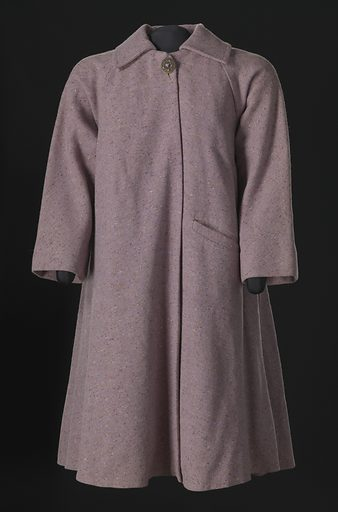 Lavender wool tweed swing coat designed by Arthur McGee. The fabric has multi-coloured wool woven flecks. The coat has a spread collar, full-length flared sleeves, and falls just below the knee. It closes at the center front neck with one (1) snap and one (1) large round metal decorative brooch-like button with a purple rhinestone at the center. The rest of the front center opening does not fasten. There is one (1) horizontal pocket sewn at the proper left front waist. Pleats are sewn at each underarm to create additional flare at the sides. The back is made extra full with a deep box pleat sewn at the center back just below the shoulders. Date: 1990s. Record ID: nmaahc_2007.3.52.1.