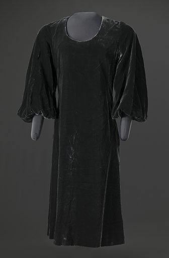 Dark grey velvet dress designed by Arthur McGee with a scoop neck, full-length balloon sleeves, and an A-line body with hemline just below the knee. There are two (2) inset pockets sewn into the side seams at each hip. The dress closes at the center back with a zipper. Only the interior yoke is lined in grey silk, the rest of the dress is not lined. There are no labels. Date: 1990s. Record ID: nmaahc_2007.3.58.