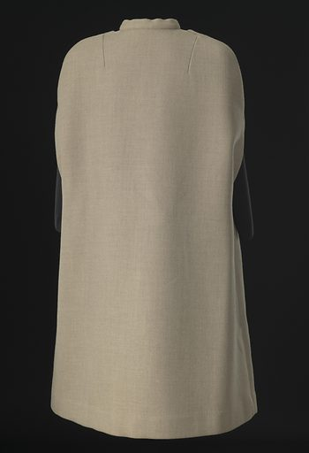 Cream wool cape designed by Arthur McGee. The cape falls below the knee and sloping shoulders with slits for the arms. It closes at the center front with ten (1) round mottled brown and cream plastic buttons. The buttonholes are hidden, being placed in the seam where the front right side placket attaches to the front right side body. There is a short standing collar with attached self-fabric ties that tie at the center front neck. The cape has two (2) patch pockets with rounded bottoms, one at each front side hip. The cape is not lined and there are no labels. Date: 1990s. Record ID: nmaahc_2007.3.68.