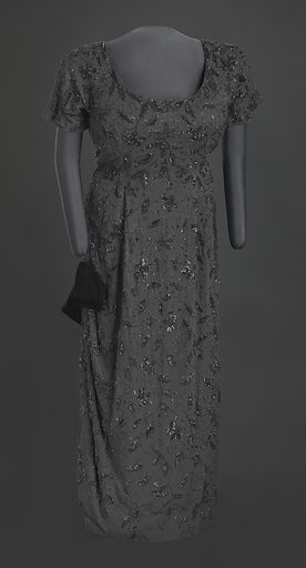 """This black beaded full-length gown was designed by Zelda Wynn and worn by Ella Fitzgerald. The dress is made from black synthetic crepe fabric that is hand beaded with black glass seed and bugle beads, and black sequins in a floral vine design. The bodice is short-sleeved and has a scoop neck in the front and a V-neck in the back. There is a metal zipper in the center back that goes to the hip, and a hook-and-eye at the top of the zipper. The gown has a princess cut waist, but there is no seam at the waist. The gown has a column skirt with a slit on the proper right side that is 24 1/2"""" high and contains a rounded hem. At the top of the slit, there is a pre-tied black velvet bow that is sewn to the dress. Date: 1940s. Record ID: nmaahc_2010.20.1."""