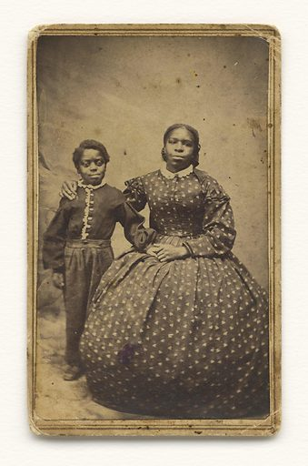 A small black-and-white print of a woman in a floral patterned dress and a white collar with her arm around a young boy in a button down shirt and pants. He stands beside her while she sits. Adhered to the back of the photograph are two red one cent tax stamps featuring a portrait of George Washington. Date: 1860s. Record ID: nmaahc_2011.30.2.