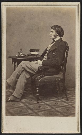 Carte-de-visite of Charles Sumner in full length seated profile. Sumner is pictured with his left profile facing the camera. His hands are resting in his lap and his left leg is crossed over his right leg at the knee. He is wearing a light coloured vest and trousers with a white shirt, dark tie, and dark jacket. Spats peak out below his pant legs, partially covering his dark coloured low-heeled shoes. His hair is moderately long and he has long sideburns. Sumner is seated in a carved armchair with an upholstered seat with a round wooden side table behind him. A stack of books, some loose papers, and possibly an inkstand are placed on the table. The floor of the room is covered in a geometric patterned carpet. There is a double-lined border printed in gold ink surrounding the outside edges of the card mount. Date: 1860s. Record ID: nmaahc_2017.30.1.