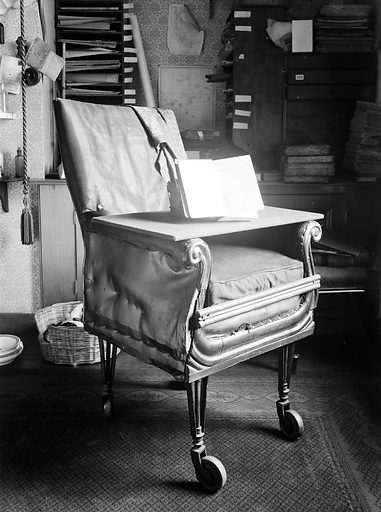 """Charles Darwin's chair and first edition of """"Origin of Species"""". Down House in Downe, Kent, is where Charles Darwin worked for 40 years and died in 1882. Work ID: k3w4mawh."""
