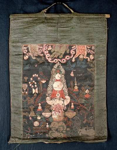 """Attributes of dPal-ldan Lha-mo in a """"rgyan tshogs"""" banner. Distemper painting by a Tibetan painter. The painting shows the attributes of a Buddhist deity. Among the attributes shown is a peacock's tail, a trident and some entrails held in the bills of flying birds. The former two items would suggest that the banner shows the attributes of dPal-ldan Lha-mo. Were it not for the entrails, the emblems could also belong to Ma-cig-ma (Ma-cig dPal-gyi Lha-mo), another form of Lha-mo, but the attributes of the latter are peaceful ones. An earlier supposition had been that the banner represents Hevajra, since one of his Tibetan epithets, Rol-pa'i-rdo-rje, is mentioned in the inscription on the back. Against this is the fact that Hevajra does not figure among the deities in another set of rgyan tshogs banners (a complete set of fifteen) in the Wellcome Library Along the top, a tiger skin, an elephant skin and a flayed human skin are suspended. The centre is taken up by a giant sacrificial cake (gtor ma) surrounded by a white radiance. There are two detached human heads. To the left of the gtor ma, a flag is surmounted by a fly whisk and a trident, and near it are a blood-filled skull bowl, a butter lamp, a peacock's tail, a garland of eleven skulls, a victorious banner, a double drum, a vajra, a bell, a vīṇā (lute), various substances offered on a low table, a wild man and three antelopes. On the right hand side are the Eight Auspicious Things: a wheel, a conch shell, an umbrella, a victory banner, two fishes, an unending knot, a lotus flower, and a vase. Underneath are a horse, a monkey, two dogs, a tiger, a snow lion, and a pair of queen's earrings. There is also a dbal (fire cone). Buddhist gods. Jiangzi Xian (China). Work ID: zwata2vq."""
