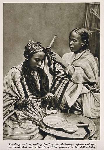 A Malagasy female hairdresser dressing the hair of a woman
