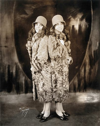Daisy and Violet Hilton, conjoined twins, wearing fur coats
