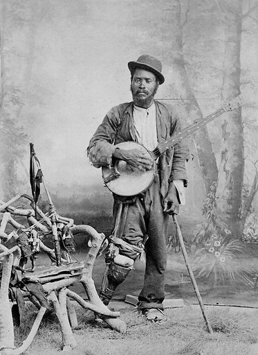 """A black banjo player with a wooden leg. Photograph, ca 1865 (?). Described as follows by Jim Bollman, The Music Emporium, Lexington, Mass., in an e-mail to the Wellcome Library on 12 February 2001: """"It is quite simply one of the most powerful 19th century banjo images that I've seen. … Obviously it's a studio portrait but unless someone could identify the painted backdrop it's practically impossible to name the studio and thus ascertain the location. My suspicion is that it's American (the rustic chair is typical of Adirondack stick furniture). If the flag or pennant attached to the chair were more visible that could give us additional clues. I frankly don't know what to make of the rag dolls on the chair. Perhaps he made them himself and """"hawked"""" them as a street peddlar. What I can tell you is that the fretless banjo is typical of the period 1850–1860s with scoop-neck, about 6 sets of hooks and nuts, """"vertical"""" fifth peg, etc. The decoration in the fingerboard and matching tailpiece is unusual but not unique for the period (they do mark the fret positions on the board). I can't tell from the photo if the instrument has flush or scribed frets on the board or simply has the rectangular inlays to show the relative positions. It is simply conjecture but he could be a veteran amputee (American Civil War) who either had an act (stage or street) playing the banjo and using the rag dolls as puppets or perhaps was dressed in rags by the photographer to produce an interesting genre photo. It's hard to believe that he would have the wherewithal to afford such an expensive sitting …. I have several thousand banjo images in my collection (probably 95% of them are unidentified)."""". Created 1860–1869. Artificial legs. Banjoists. African American veterans. Banjo. Bentwood furniture. United States. Work ID: n3733yh6."""