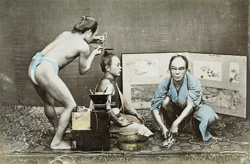 Japan: a hairdresser wearing a loin cloth at work on a kneeling man