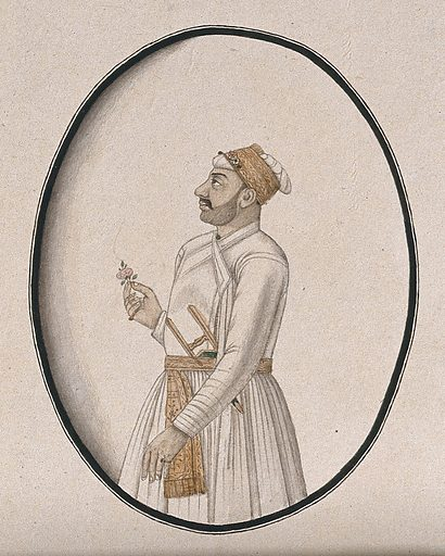 A Mughal courtier carrying a dagger and holding a flower. Watercolour drawing by an Indian artist. Work ID: p9krnccq.