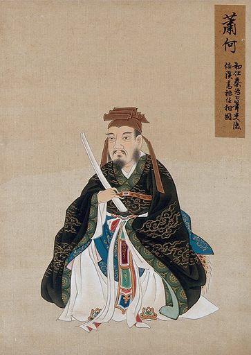 A Chinese figure wearing black silk robes with a green border, richly decorated with cloud scroll designs in gold thread. Painting by a Chinese artist, ca 1850. Created 1850. Work ID: xmxapgzq.