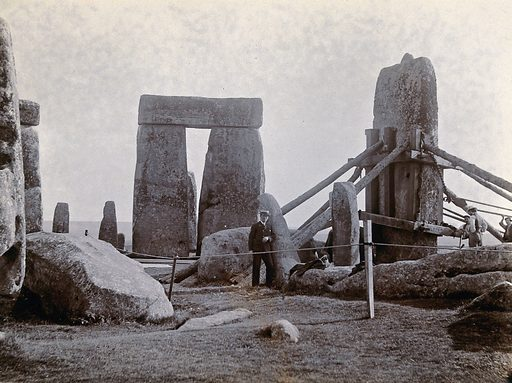 Stonehenge, England: the straightening of a leaning stone which is attached to a wooden frame and supported by beams: …