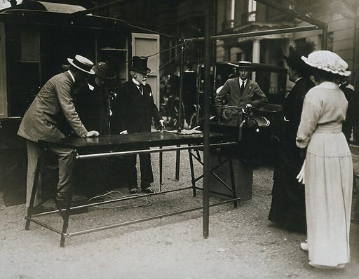 Ambulance x-ray equipment on display in the street, with several onlookers. Photograph, ca 1910. Created 1910. Work ID: zaztx636.