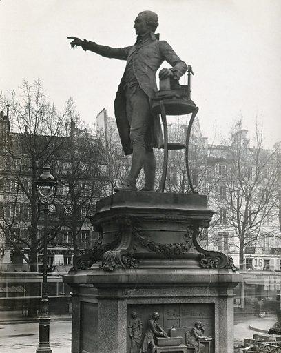 Antoine Lavoisier: statue; Lavoisier in his laboratory: bas-relief at base of plinth: Place de la Madeleine, Paris. Photograph, ca 1930, of a bronze sculpture and bas-relief by Ernest-Louis Barrias, ca 1880. Created 1930. Work ID: v9htnc7k.