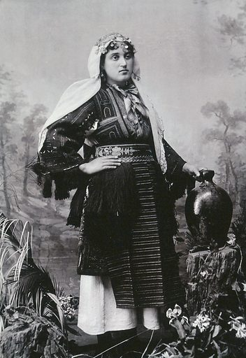 A Bulgarian woman, portrayed in national dress, with a water jug, in a studio setting. Photograph, first quarter of the twentieth century. Work ID: ubebhg5s.