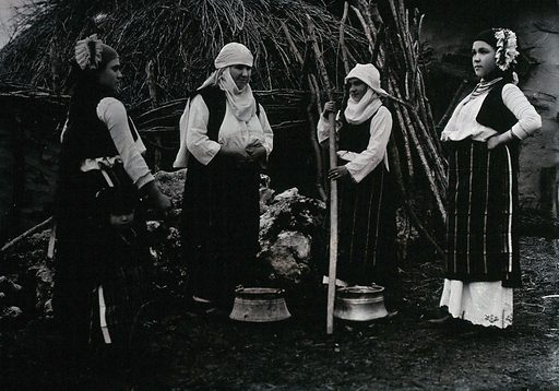 Four Bulgarian women, portrayed wearing national dress, one with a yoke-pole and two water pails, in a village setting. Photograph. Ethnic costume. Water. Women. Bulgaria. Work ID: rjd7jf96.