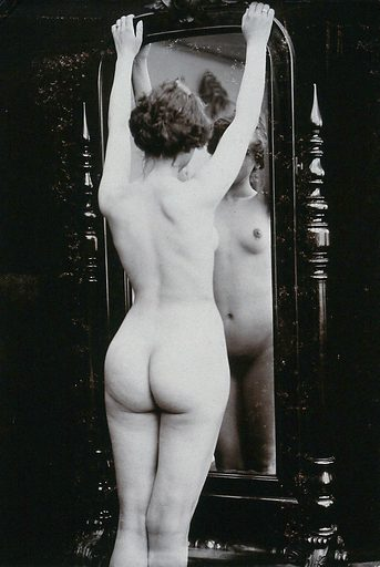 A young woman, almost full-length, posing naked in a photographic studio, looking at herself in a cheval-glass. Photograph, ca1900. Work ID: qxwmjpbz.