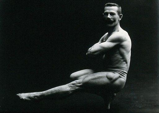 "A male bodybuilder wearing bathing trunks, striking a ""Cossack dance"" pose, in a studio setting. Photograph by Hana Studios, ca1899–1908. Contributors: George Henry Hana; Hana Studios Ltd. Work ID: tfetzfsd."