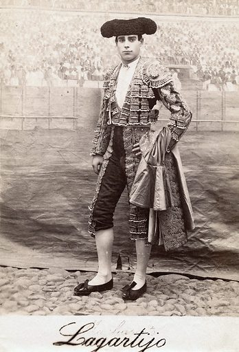 """A bullfighter, Rafael Molina Sanchez """"Lagartijo"""", posing in front of a painted backdrop of a bullring crowd, in a cobbled courtyard. Photograph, ca1890/1910. Bullfighters. Costume. Spain. Lagartijo. Work ID: pdr2rj9p."""