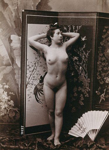A young woman, with her hands behind her head, posing naked against an oriental screen. Photograph, ca1900. Work ID: wywhjpbn.