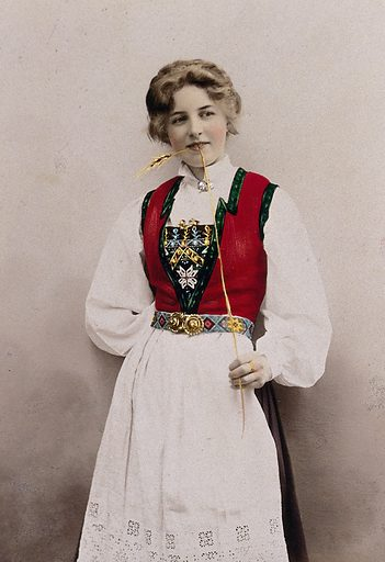 A young Norwegian woman, posing in a photographic studio wearing peasant dress. Coloured photograph by S Lund, 1903. Contributors: Solveig Lund. Work ID: bgzm9skw.