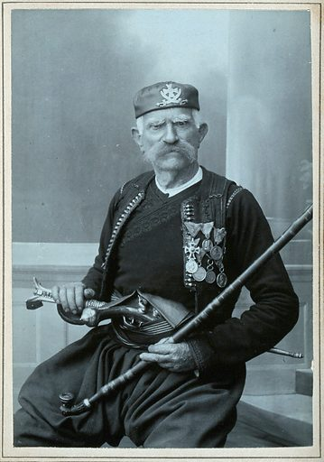 An elderly Serbian man, wearing national dress with many medals, with a pistol in his belt and holding a tobacco pipe. Photograph by D Djordjevic, first quarter of the twentieth century. Medals. Ethnic costume. Pistols. Muzzle-loading firearms. Tobacco pipes. Cetinje (Montenegro). Contributors: Djordjia. Djordjevic. Work ID: vdzjdj9h.