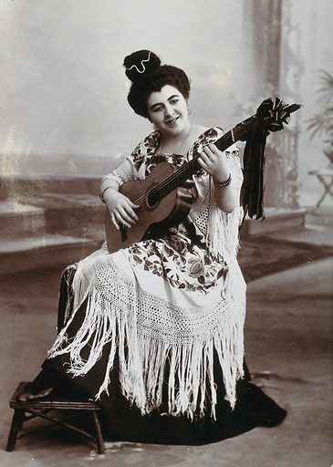 A seated woman, playing a guitar, wearing a fringed shawl. Photograph, ca1900. The same woman as seen in 530413i. Music. Women. Flamenco. Spain. Work ID: svw6vwj7.