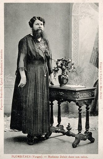 "Madame Delait, the bearded woman of Plombières, head and shoulders portrait. Photographic postcard by Scherr, 1923. Madame Delait was proprietor, after the death of her husband in 1928, of the ""Café de la femme au barbe"" at Thaon-les-Vosges. Created 1923. Ethnology. Hypertrichosis. Plombières-les-Bains (France). Clementine Delait (1865–1939). Contributors: Scherr (active 1923). Work ID: yc3nnaqm."