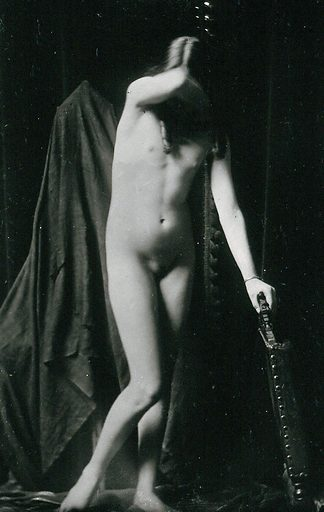 An adolescent girl, posing naked leaning on the back of a chair, in a makeshift photographic studio. Photographic postcard, ca1920. Work ID: uj4mxphc.