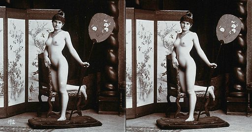 A young woman posing naked in a photographic studio, kneeling on a chair holding a fan, in front of a screen. Stereo photograph, ca1900. Work ID: tabpv428.