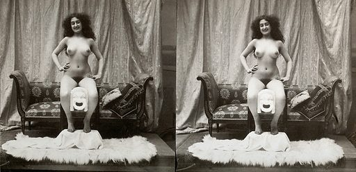 A young woman, full-length, posed naked sitting on a table with her feet on a fur-covered stool, in a photographic studio. Photograph, ca1900. The same woman as seen in 531161i. She seems to be gripping a Greek mask of comedy between her knees. Women. Fur. Ethnology. Female nude in art. Photography of the nude. Work ID: npnyuxkj.