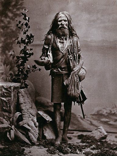An old Indian man, wearing many beads, and carrying a begging bowl and an umbrella, in a studio setting. Photograph, ca1900. Work ID: dx4pjqa5.