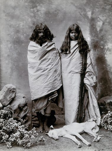 A man and woman of the Toda tribe standing in a photographic studio, with a dog lying at their feet. Photograph, ca1900. Ethnology. Ethnic costume. Dogs. Toda (Indic people). Beards. India. Work ID: mpb5d7bz.