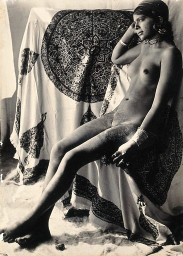 A young Kashmiri girl, posing naked sitting back on some fabric. Photograph, ca1900. The pubic hair is retouched out on the negative. Ethnology. Jewelry. Photography of the nude. Female nude in art. India. Work ID: sv3uswwq.
