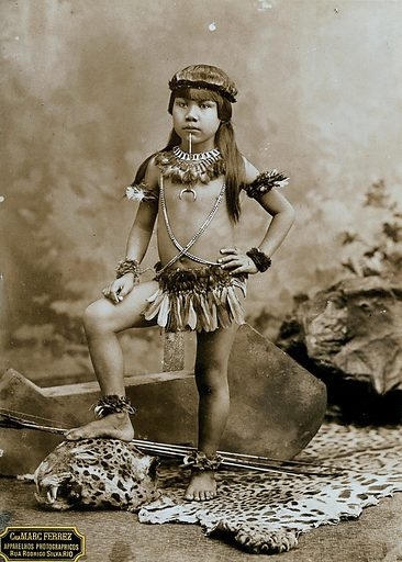A child of an Amazonian Indian tribe, standing on a leopard skin, in a photographic studio. Photograph, ca1900, by Marc Ferrez. Contributors: Marc Ferrez; Casa Marc Ferrez. Work ID: ur6ejvdz.