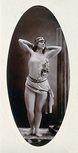 A young woman posing semi-naked, standing on a podium beside a truncated classical column in a photographic studio. Photograph by Portland Studio, ca1903. Contributors: Portland Studio. Work ID: a4ppzypk.