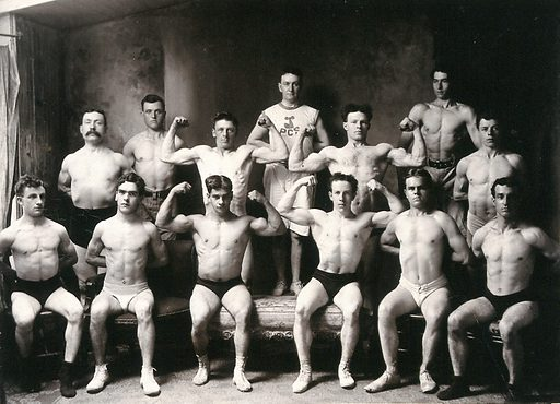 Male body-builders from the Physical Culture Society of Montreal posing semi-naked with their trainer, in a photographic studio. Photograph by Gordon, 1905. Created 1905. Male nude in art. Bodybuilders. Montréal (Québec). Physical Culture Society of Montreal. Contributors: Gordon. Work ID: h8mf3dbg.