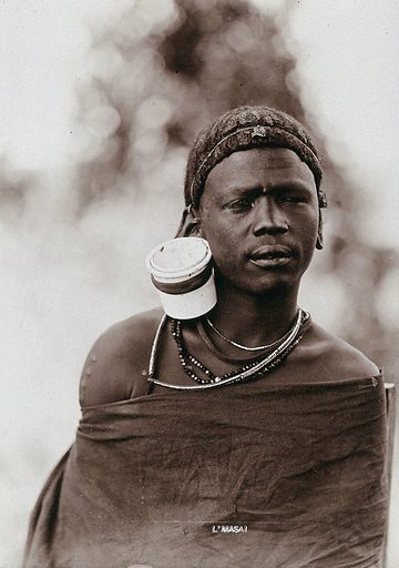 A young Masai tribesman, wearing a very large earring. Photograph, ca1900. Work ID: dzkrqh2p.