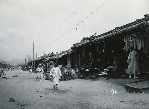 A line of shops beside a dusty street, with telegraph poles overhead, in Korea. Photograph, ca1900. Ethnology. Retail. Stores. Workshops. Work ID: fqwx2phm.