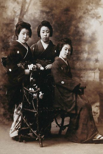 Three young women posing in a photographic studio, one seated on a bench, in front of a painted backdrop of a rural scene. Photograph by K Ogawa, first decade of the twentieth century. Contributors: Kazuma Ogawa. Work ID: t2qx24v4.