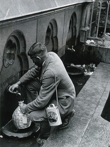 Lourdes, France: a pilgrim fills a flask with sacred spring water from a tap. Photograph, ca 1937. Created 1937. Work ID: r9qhrhtg.