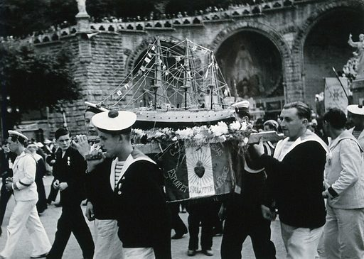 Lourdes, France: sailors carrying a model of a ship amidst crowds of pilgrims. Photograph, ca 1937. Created 1937. Work ID: jjd8b27f.