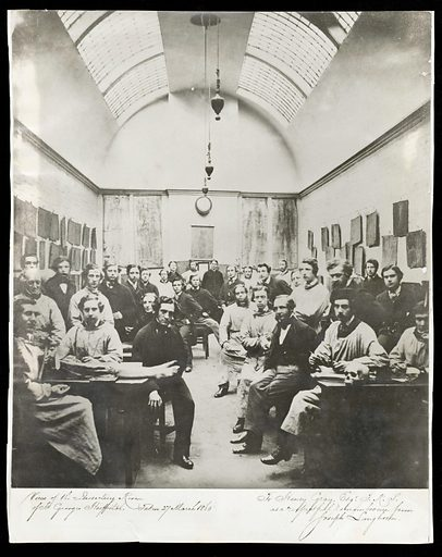 Saint George's Hospital, London: the dissecting room with students and lecturers, including Henry Gray. Photograph. Henry Gray, author of Gray's Anatomy, sits next to the cadaver's feet. Anatomical prints are suspended on the walls. The room is top-lit by an arched sky-light. Created between 1900 and 1999?. Dissection. Anatomy. Henry Gray (1825–1861). St George's Hospital (London, England). Medical School. Work ID: s9335xbp.