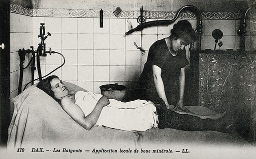 Mud being applied on the leg of a patient of a thermal establishment in Dax, France. Photographic postcard, ca 1920. Created 1920?. Work ID: b6g9aza9.