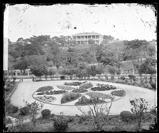 East Point, Hong Kong. Photograph by John Thomson, 1868/1871. Building and garden, situated at East Point, were the property of Jardine, Matheson & Co The building was the house of a director of this company. Newly planted circular ornamental garden in foreground, colonial house across the street on hill. Contributors: J Thomson. Work ID: n6mvb5cv.