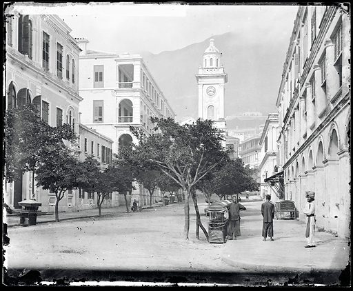 """Peddar Street, Hong Kong. Photograph by John Thomson, 1868/1871. Street scene looking south towards the clock-tower, clock indicates 815 [am?]. Right foreground, three figures, one wearing a short sword and Sikh turban. To right, waggon inscribed """"Wedding & fancy cakes, soda & tiffin biscuit"""". Jardine, Matheson's office is the building on the right, Dent's office is on the left. Contributors: J Thomson. Work ID: h4cf4pxg."""