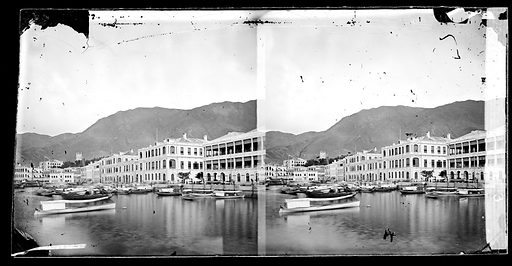 The Bund, Hong Kong. Photograph by John Thomson, 1868/1871. View from pier or boat towards land looking towards the east. The street is known as the Praya or Des Voeux Road. The building on the right is the office of Jardine, Matheson & Co The one next door is the office of Dent & Co, their chief rival in the opium trade. Contributors: J Thomson. Work ID: b3f3gefv.