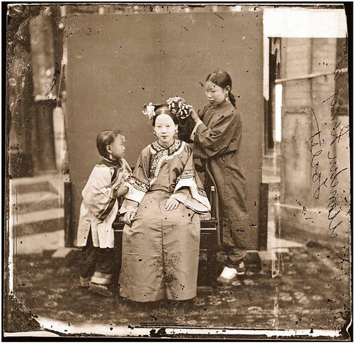 China: a Manchu lady having her hair dressed by her servant girl, Beijing. Photograph by John Thomson, 1869. Contributors: J Thomson. Work ID: jrjn2zb9.