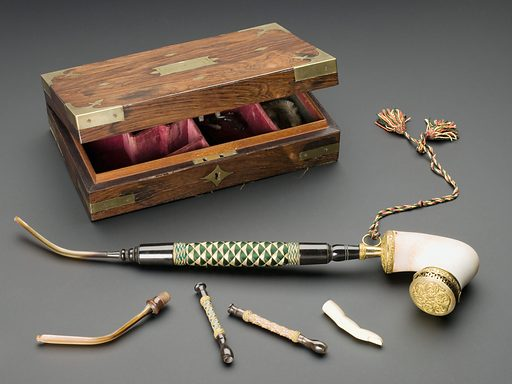 Travelling smoking set, Europe, 1815–1820. The set contains everything for a travelling gentleman's smoking needs in the early 1800s. This includes a large meerschaum pipe bowl (meerschaum is a clay like material), a choice of three stems and seven mouthpieces, one tinder pouch with steel flint attached (to light the pipe), one ivory tamper in the shape of a finger (to pack tobacco into the pipe bowl), and one long slender bristle brush for cleaning the pipe. The gentleman smoker came to the fore during the 1800s. In a time before the mass production of cheap cigarettes, pipe smoking was the preferred method and among wealthier gentlemen it became a serious hobby. Aside from the numerous varieties and mixtures of tobacco and the many pipe related accessories, there was a large range of books and periodicals devoted to the habit. Contributors: Science Museum, London. Work ID: aj7fnb6y.