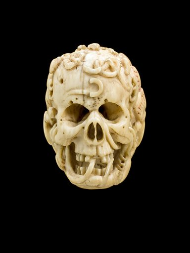 Ivory model of half a human head, half a skull, Europe, undated. Carved from ivory, this model shows a human male face on one side and a skull crawling with worms on the other. A banner with an inscription runs around the man's face. This type of model is thought to be a memento mori – literally a reminder of death and the shortness of life. The skull was the symbol of death from the 1500s onwards. Previously death was represented as a skeleton accompanied by a living victim. Contributors: Science Museum, London. Work ID: z3syda8c.